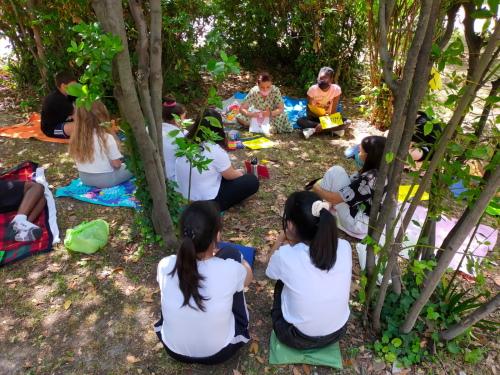 Gli alunni seduti fra gli alberi del giardino della scuola con la docente di italiano
