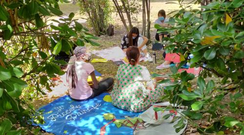 """Gli alunni seduti fra gli alberi del giardino della scuola seduti su un telo mare ispirato al romanzo """"Il Piccolo Principe"""""""